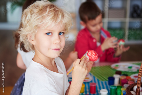 Leinwanddruck Bild Portrait of smiling boy painting easter eggs