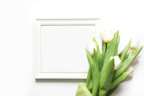 Frame for text and white tulip on white. Top view with copy space.