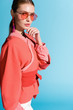 attractive woman in trendy living coral clothing and sunglasses posing isolated on blue