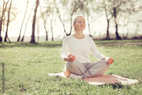 Leinwanddruck Bild Relaxed mature woman doing yoga in park