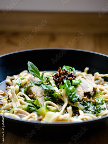 Thai Chinese style hot stewed Duck noodles soup served in a black bowl, egg noodles and chili oil on top. - 249062115