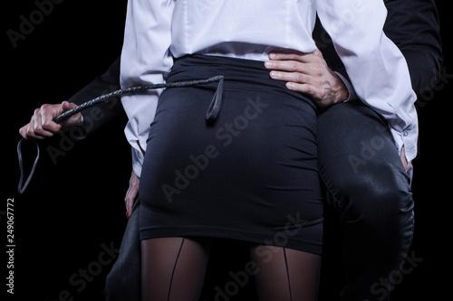 Leinwanddruck Bild Man hand holding whip on woman ass in mini skirt
