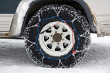 Snow chains on the wheel of a 4X4 vehicle poster