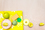 Spa concept, natural ingredients. Bath towel, sea salt with lime, apple, olive and mint soap, sponge. On a stone background, top view