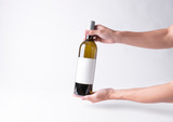 Hand holding a wine bottle for mock-up. Blank Label on a gray background. - 249080992