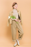 trendy woman wearing beret and holding bouquet isolated on beige