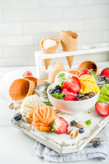 Colorful fruit and berry, nut, chocolate and vanilla ice cream, with waffle ice-cream cones, with fresh fruit and berries, top view copy space white marble background