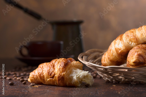 Fresh and tasty croissant  and cup of coffee on old copper background.