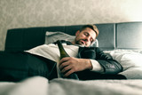 Drunk businessman in suit lying in the bed and sleeping with bottle of alcohol in his hand. Alcohol abuse concept. - 249093779