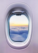 Airplane interior with window view of sunset above clouds. - 249094131