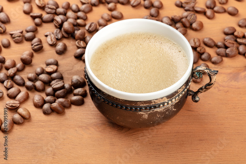 Coffee in a vintage cup with coffee beans on a dark rustic wooden background © laplateresca