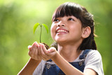 A girl holding a young plant in her hands with a hope of good environment