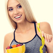 Woman in sportswear with tape measure and fruits