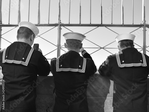 3 united states navy sailors on top of the Empire State Building looking at the views