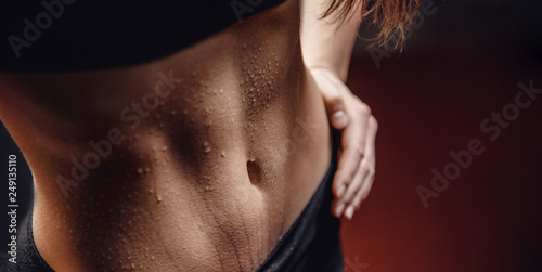 Concept sweat after exercise. Inflated body fitness of young woman, abdominal muscles dices