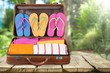Retro suitcase with travel objects on wooden board on background