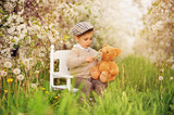 A little boy with a teddy bear in a blooming cherry orchard. Child and spring. A teddy bear smelling the flowers. - 249178526