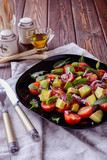 Colorful and tasty salad with avocado, cherry tomatoes and mozzarella on a black dish next to a fork and knife served to eat