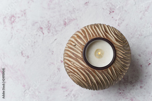 Tea candle in handmade wooden candleholder on light pink Valentine background © Lukas
