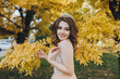 Quadro A smiling bride in a beige dress is standing in a park with yellow leaves. The princess with a crown enjoys the fall. Wedding portrait of a beautiful bride with brown hair. Wedding photography.
