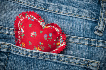 Closeup of red fabric shaped heart in blue jeans pocket