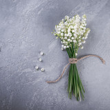 Lily of the valley flowers on gray background, top view