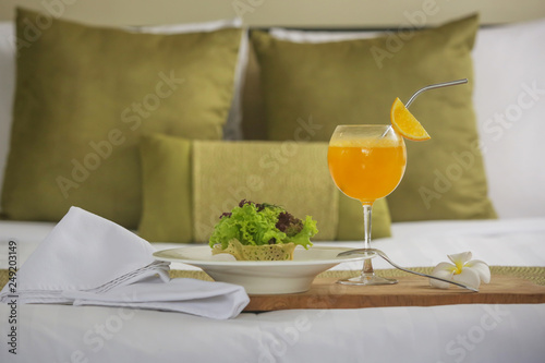 A portion of avocado salad with lettuce and freshly squeezed orange juice served in a hotel room, room service, healthy start of the day © triocean