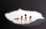 Miniature women changing clothes. The concept of stealthy criminal behavior.
