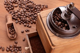 A closeup of a vintage coffee grinder with roasted coffee beans in the blurred background, selective focus - 249253555