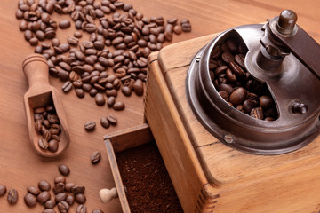 A closeup of a vintage coffee grinder with roasted coffee beans in the blurred background, selective focus