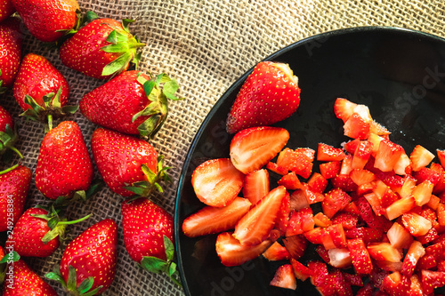 Foto Murales homemade juicy strawberries, whole and sliced, lay on a rough canvas napkin on a wooden surface
