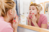 Happy woman washing her face under sink - 249259929