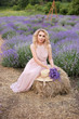 Pretty girl in a lavender field holding a bouquet of lavender.