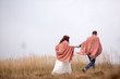 bride and groom wrapped in blanket in yellow field