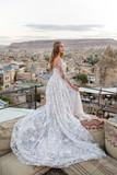 Beautiful blonde bride in white long dress posing in Cappadocia