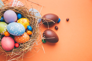Colorful easter eggs with chocolate and candies in a nest on a orange background © asife