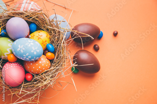 Colorful easter eggs with chocolate and candies in a nest on a orange background - 249285574