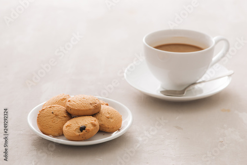 Coffee. White porcelain cup of freshly brewed coffee top view close-up arranged with  biscuits, spoon and plate on light background - 249292324