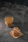 Tasty cookies and glass of coffee with milk on a plain background