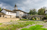 Old bridge (also called hunchback bridge) on the Trevnenska river and the clock tower in town of Tryavna
