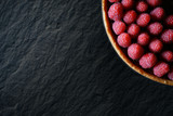 Top view of beautiful raspberry and chocolate tart on slate with text space