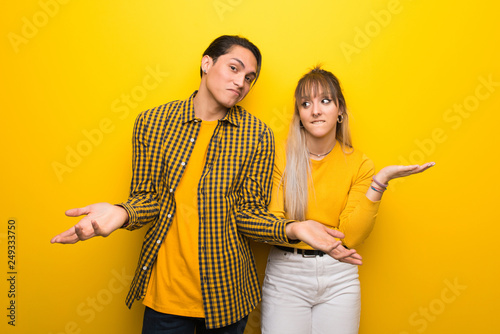 Young couple over vibrant yellow background making unimportant gesture while lifting the shoulders