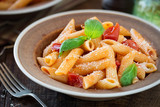Plate of pasta penne with cherry tomato sauce, fresh basil and grated parmesan cheese - Pasta al Pomodoro. Served in rustic plates for dinner for two - 249343969