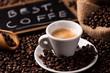 Leinwandbild Motiv Expresso coffee cup close-up over dark roasted coffee beans