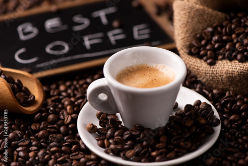 Expresso coffee cup close-up over dark roasted coffee beans - 249353785
