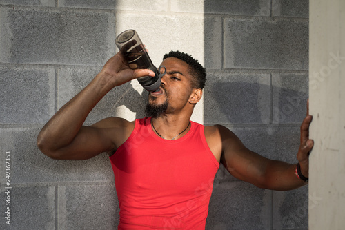 Athlete taking a urban workout break for resting and drinking water.