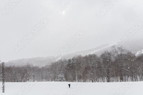 mata magnetyczna Solitary skier hiking towards the ski trails.