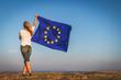 EU flag in female hands. Woman holding waving European Union flag against blue sky