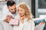 Handsome man presenting gift to surprised blonde woman