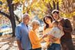 Leinwanddruck Bild - Multl generation family in autumn park having fun